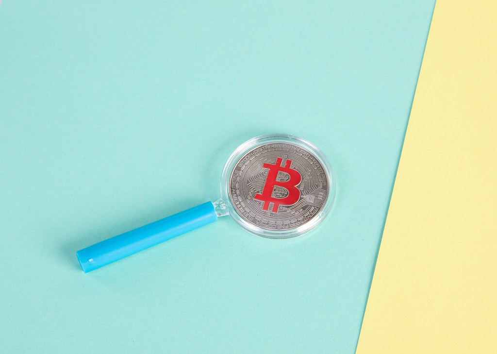 Magnifying glass over sIlver Bitcoin coin