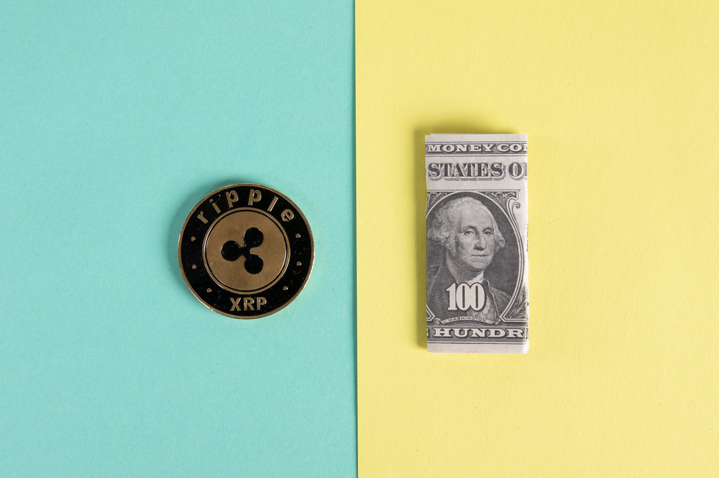 Ripple coin and folded one hundred dollar banknote