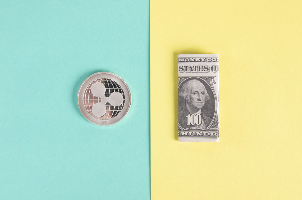 Silver Ripple coin and folded one hundred dollar banknote