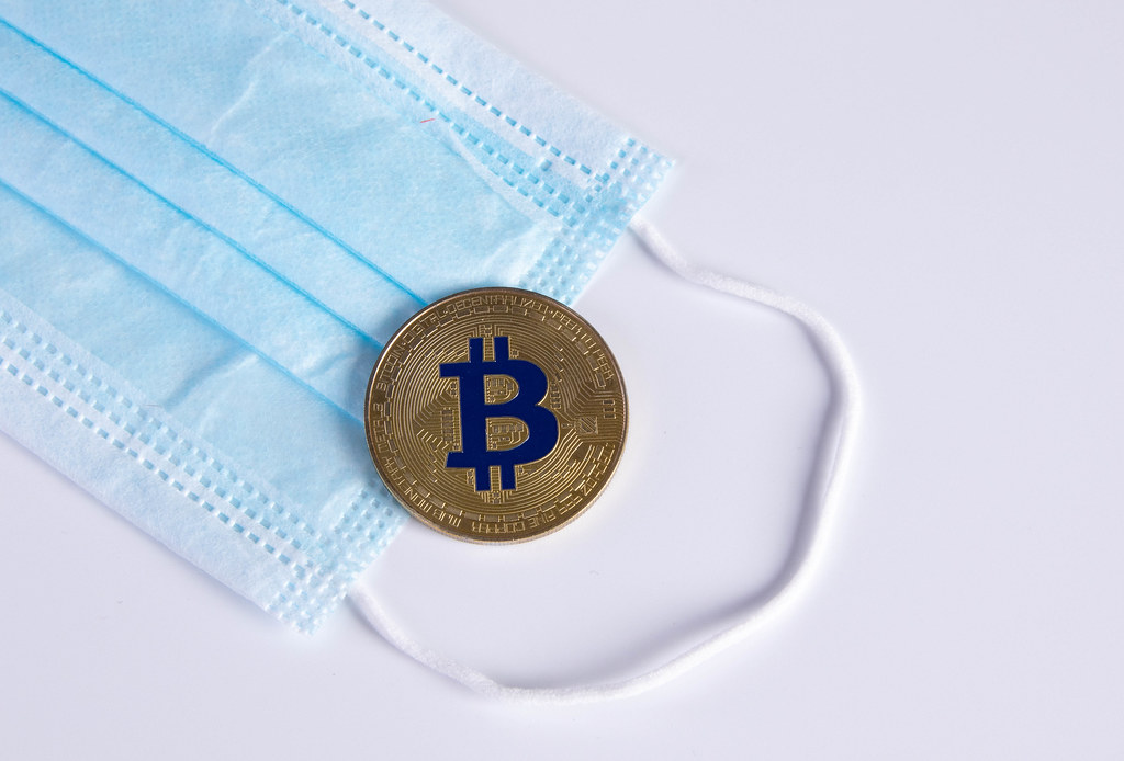 Golden Bitcoin with protective face mask on white background