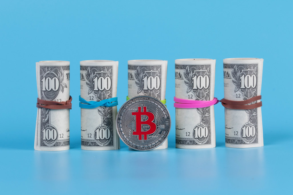 American US dollar bills in rolls with silver Bitcoin coin ob blue background