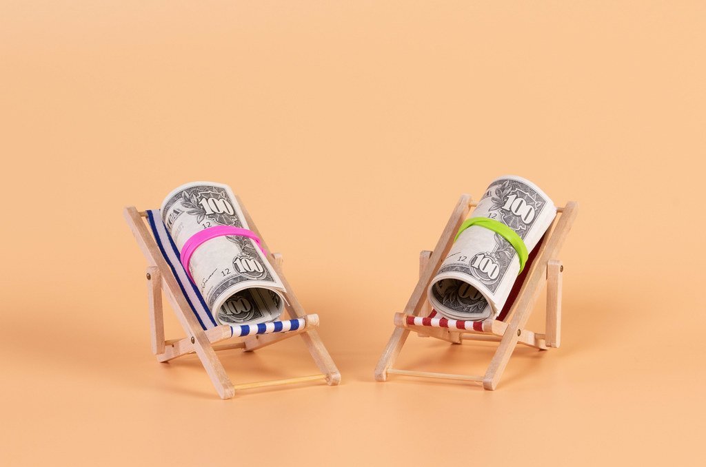 Rolls of dollar banknotes lying in a deck chair