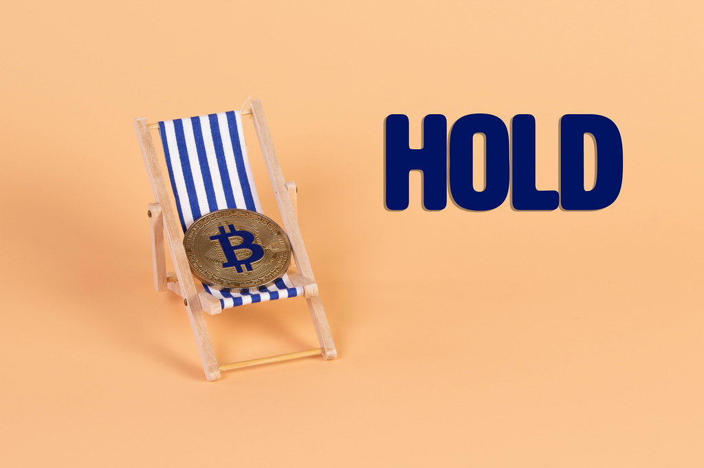 Golden Bitcoin coin lying in a deck chair with Hold text