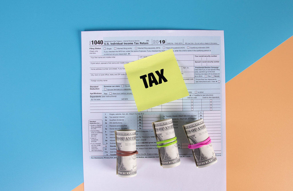 USA tax form 1040 for US individual tax return with money rolls and sticky note with Tax text