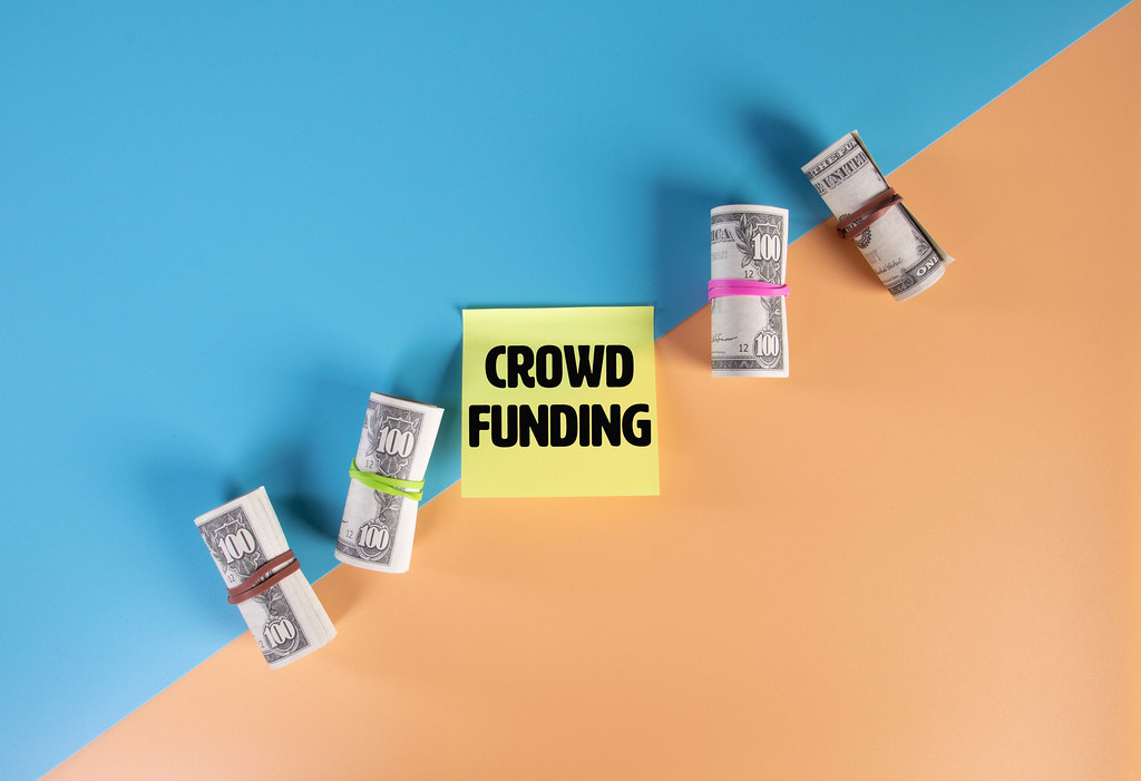 Money rolls and sticky note with Crowd Funding text