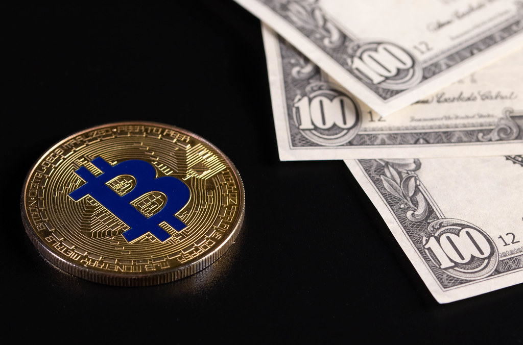 Golden Bitcoin coin with US dollar banknotes