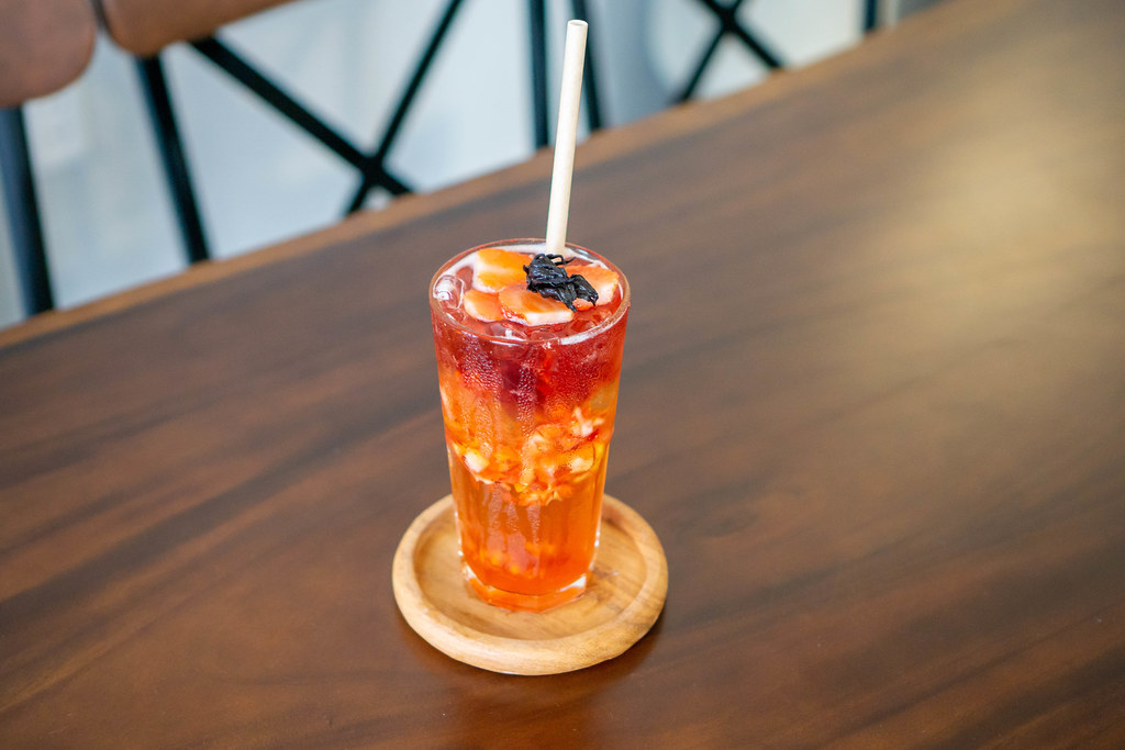 Strawberry Iced Oolong Tea with Strawberry Jelly, Sliced Strawberries and Dried Hibiscus on a Wooden Table in a Modern Cafe