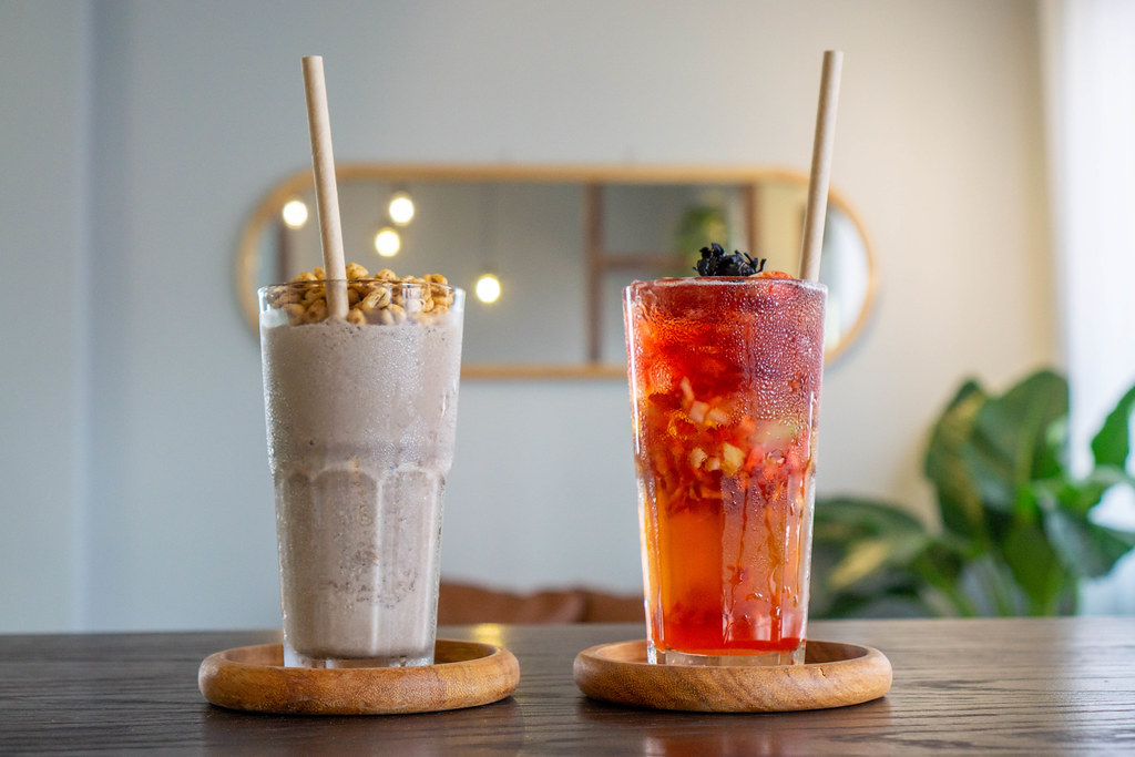 Close Up Photo of Cookies and Cream Milkshake and Strawberry Iced Tea in Cocktail Glasses on Wooden Saucers with Paper Straws in a Cafe
