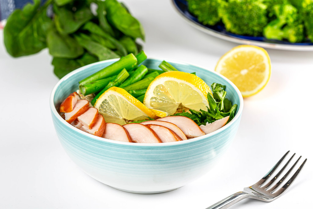 Food background with a bowl of oatmeal, chicken fillet and herbs