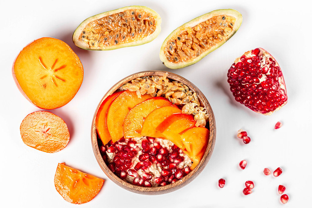Top view, bowl of oatmeal on white background with pomegranate, persimmon and kuruba