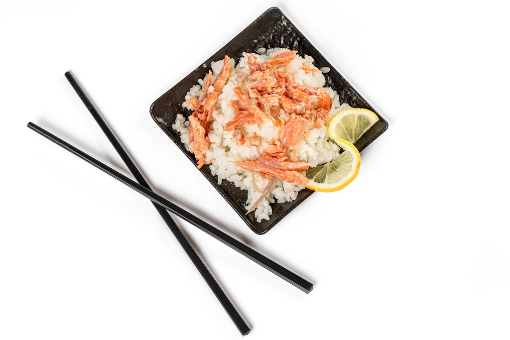Steamed rice with salmon fillet and lemon, top view