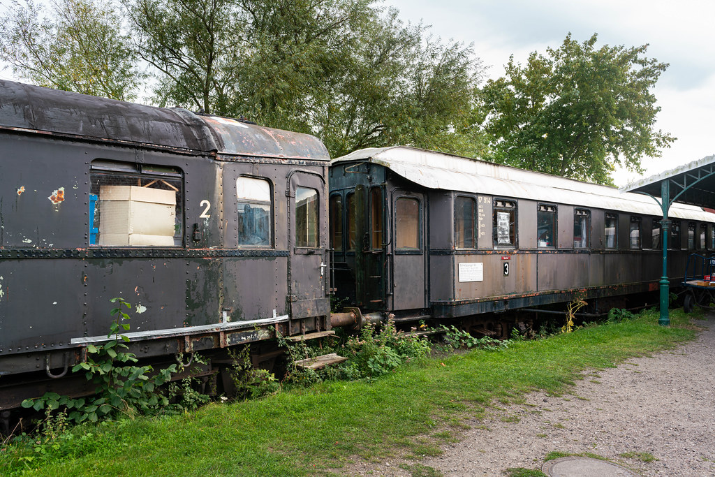 Old abandoned German train cars covered in rust and grass