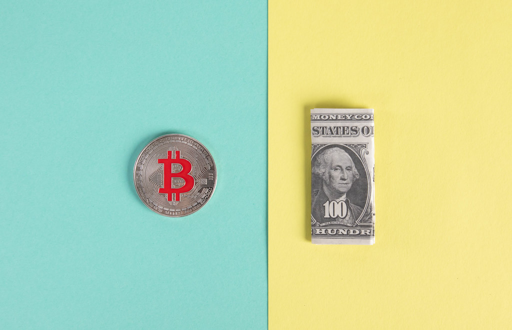 SIlver Bitcoin coin and folded one hundred dollar banknote