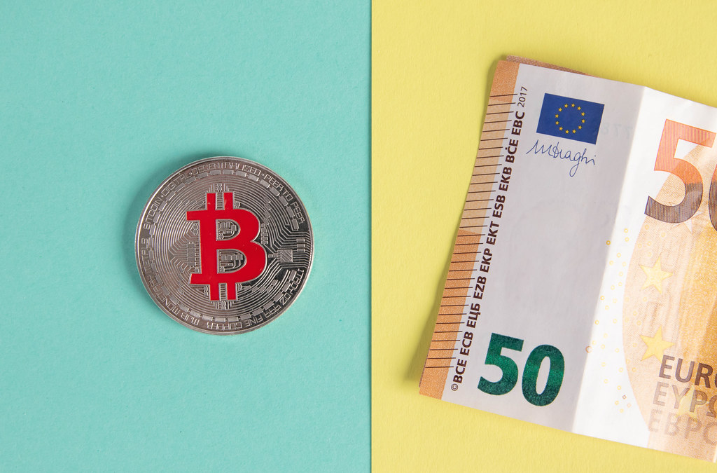 Bitcoin coin and folded 50 Euro banknote