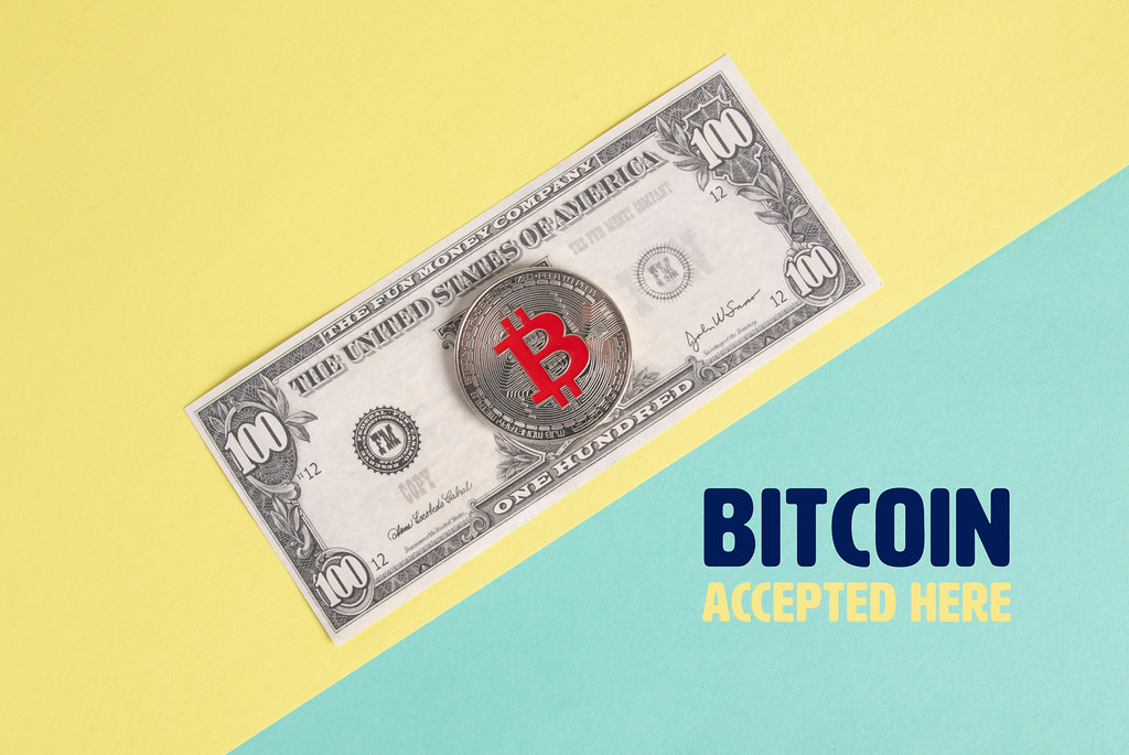 Silver Bitcoin coin on the  one hundred dollar banknote and Bitcoin accepted here text