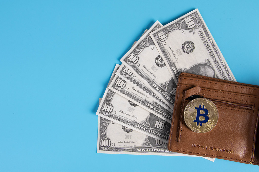 Open wallet with dollar banknotes and golden Bitcoin coin