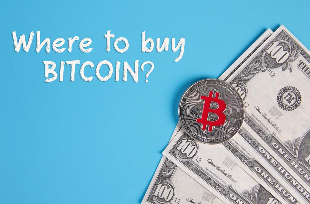Dollar banknotes with silver Bitcoin coin and Where to buy Bitcoin text