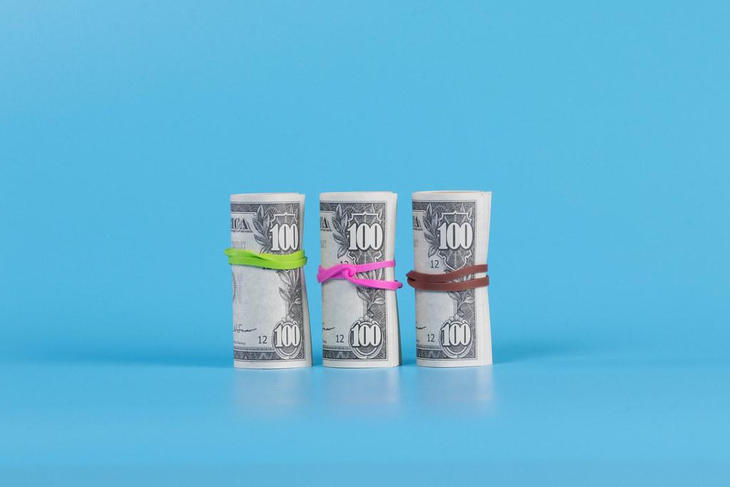 American US dollar bills in rolls on blue background