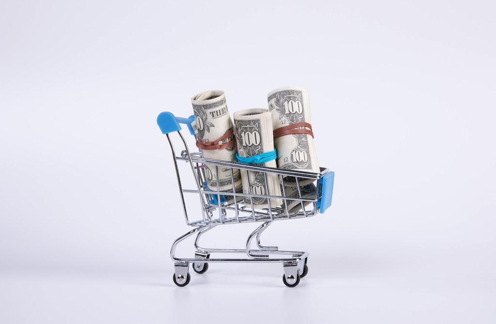 US dollar bills in rolls inside supermarket shopping cart