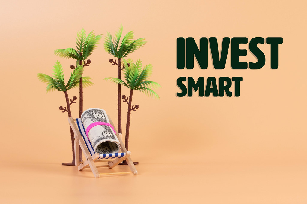 Roll of dollar banknotes in a deck chair with Invest Smart text
