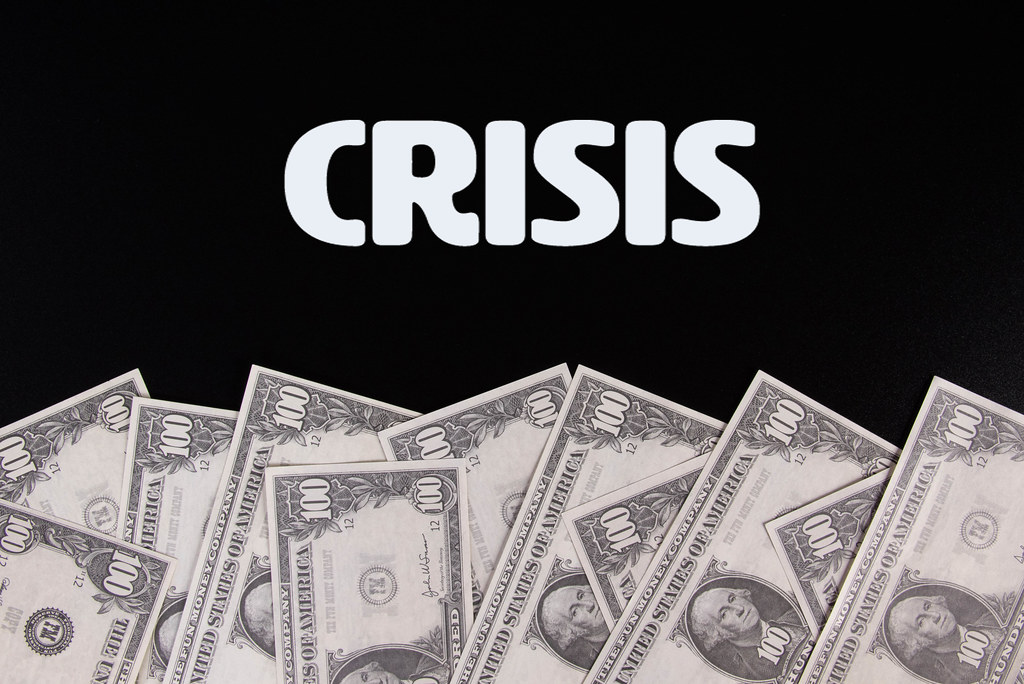 Dollar banknotes with Crisis text on black background