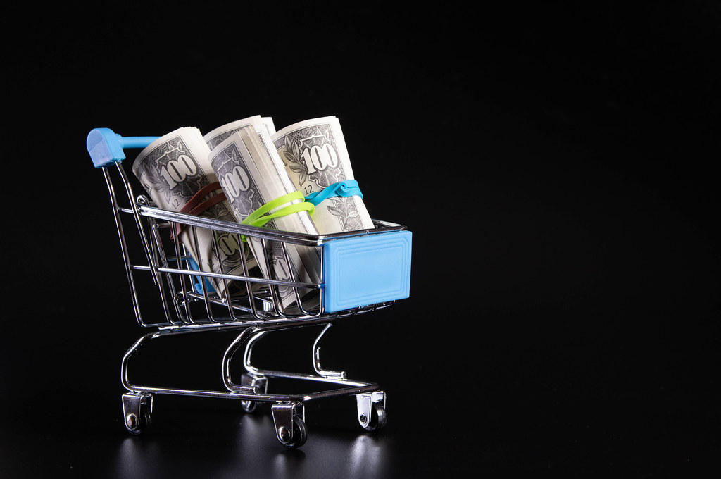 Rolls of dollar banknotes in shopping cart on black background