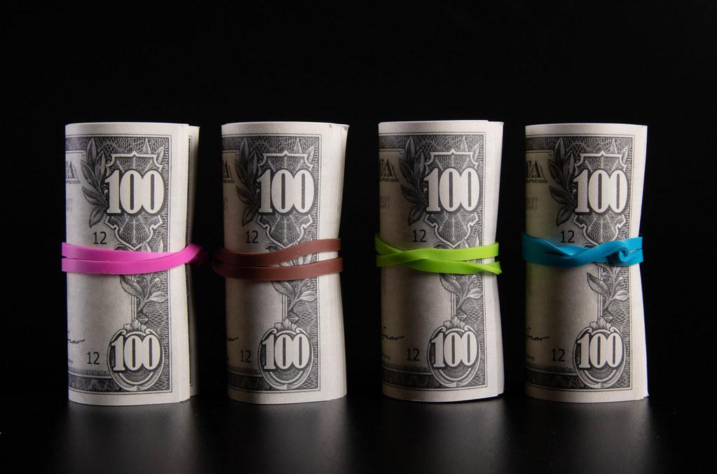 Rolls of dollar banknotes on black background