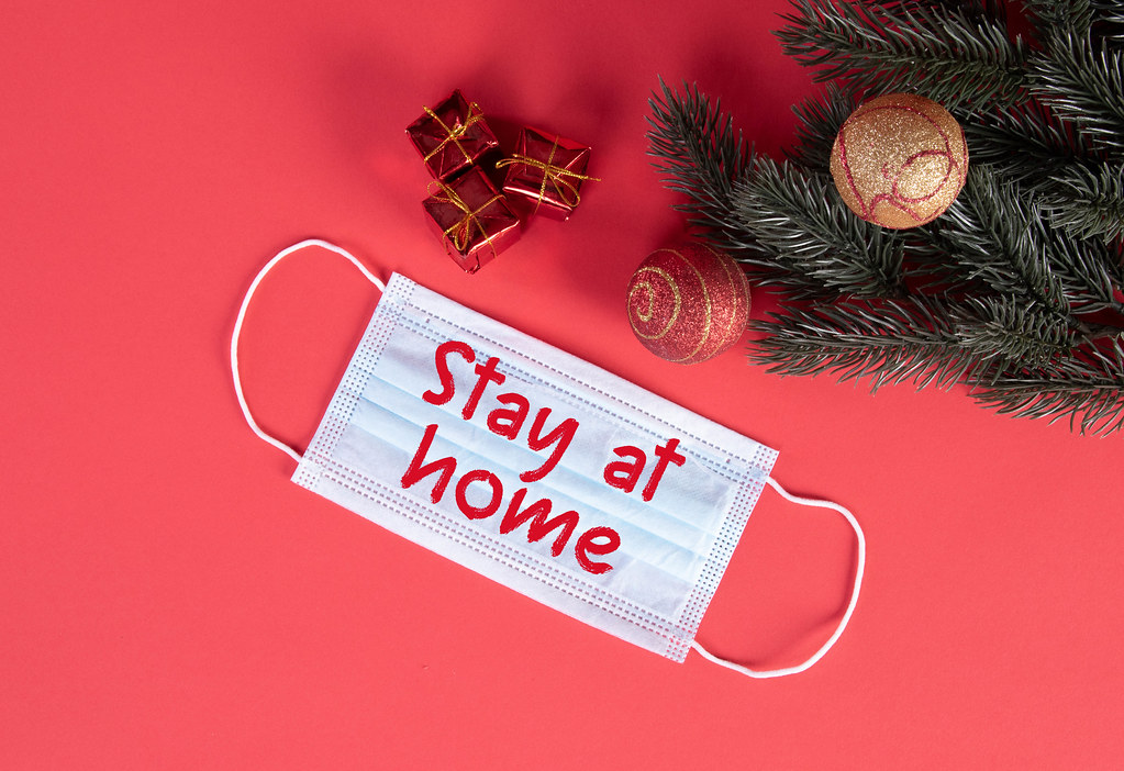 Protective face mask with Stay at Home text and Christmas decorations on red blue background
