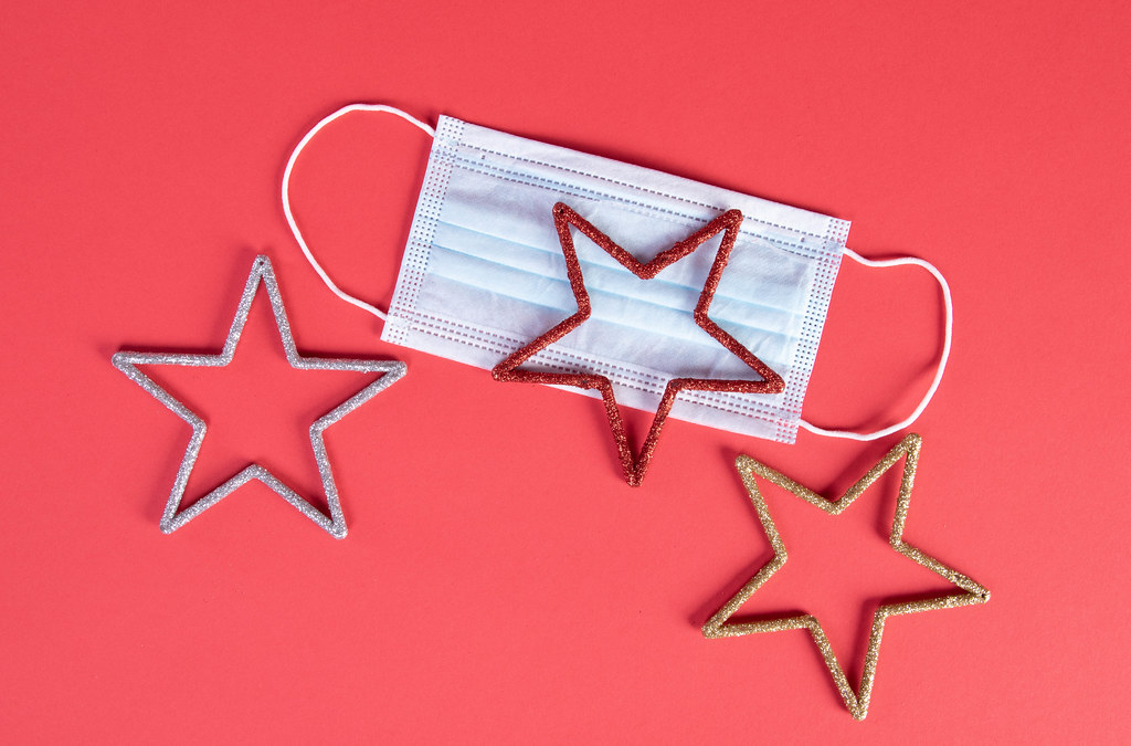 Medical face mask and stars on red background