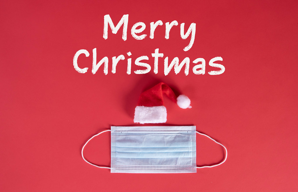 Santa Claus hat with medical face mask and Merry Christmas text on red background