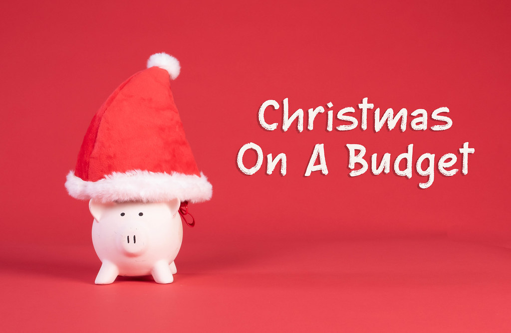 Piggy bank with Christmas hat and Christmas on a budget text on red background