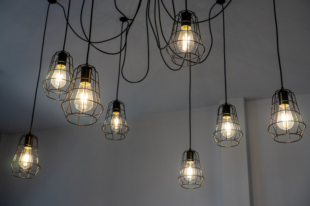 Creative and Decorative Hanging Ceiling Lamps with Bright Light Bulbs and Cables in a Cafe Seating Space