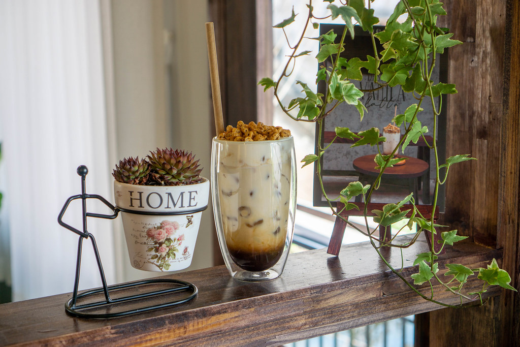 Iced Dessert Vanilla Latte with Espresso, Milk and Puffed Rice in a Double Wall Latte Glass on a Shelf with Plants