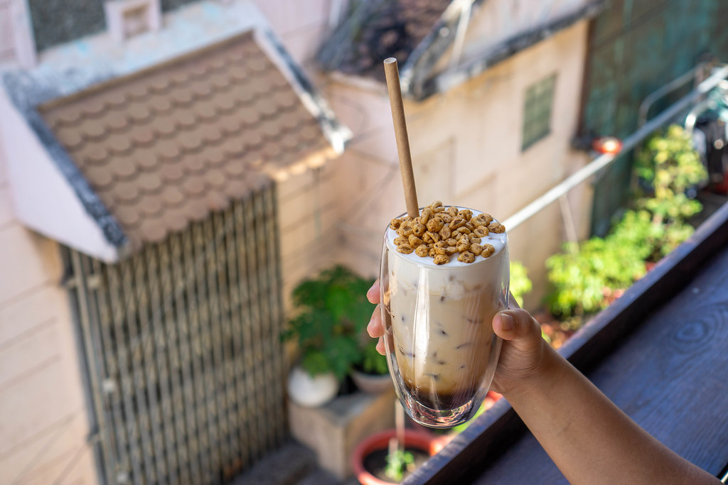 Person holding a Double Wall Latte Glass with Iced Vanilla Latte topped with Puffed Rice Cereals on a Balcony of a Cafe