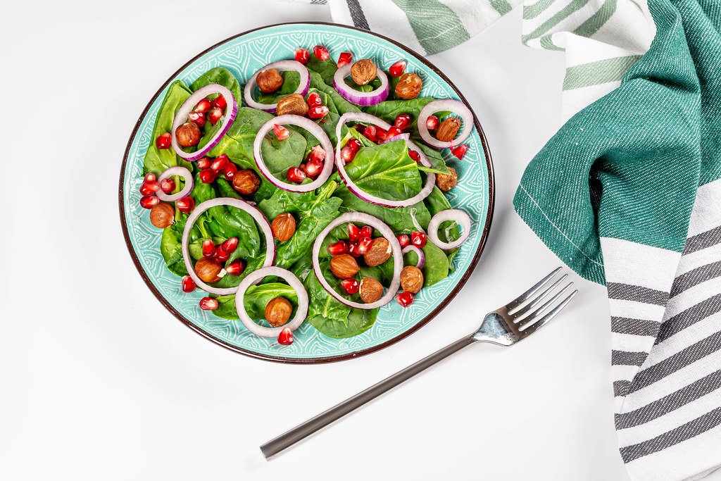 Top view, salad with spinach and pomegranate