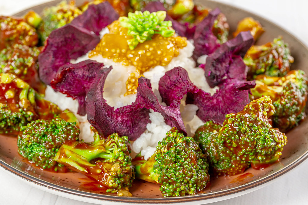 Close-up, broccoli in tomato sauce with rice, purple carrots and guava