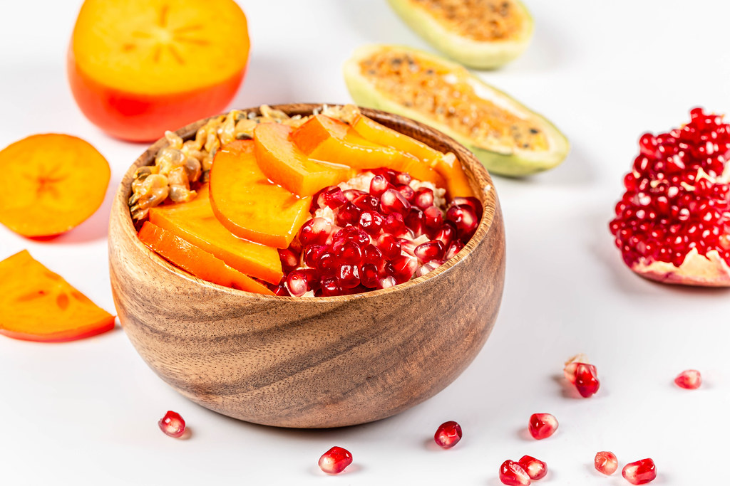 Bowl of oatmeal with pomegranate, persimmon and kuruba