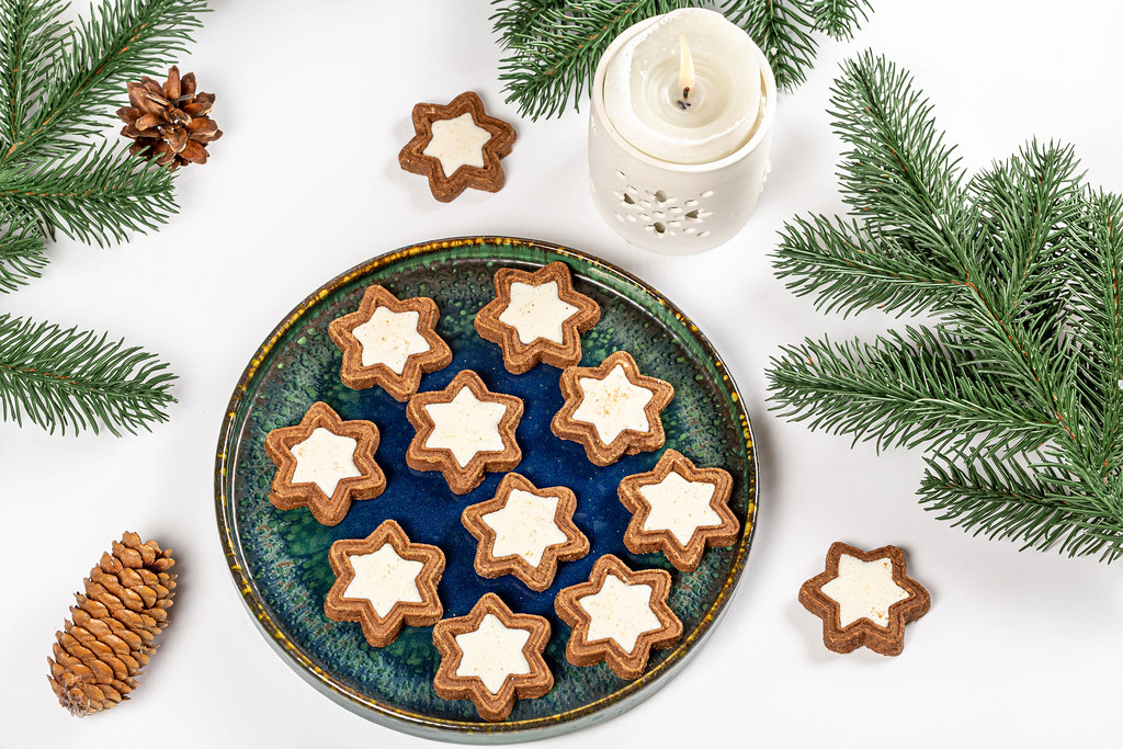Top view, cookies in the shape of a star on a white background with branches of a christmas tree