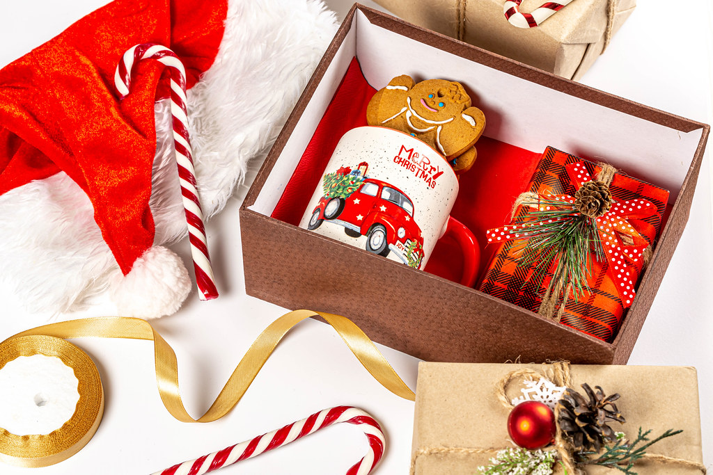 Open christmas gift box with cup, gingerbread and present