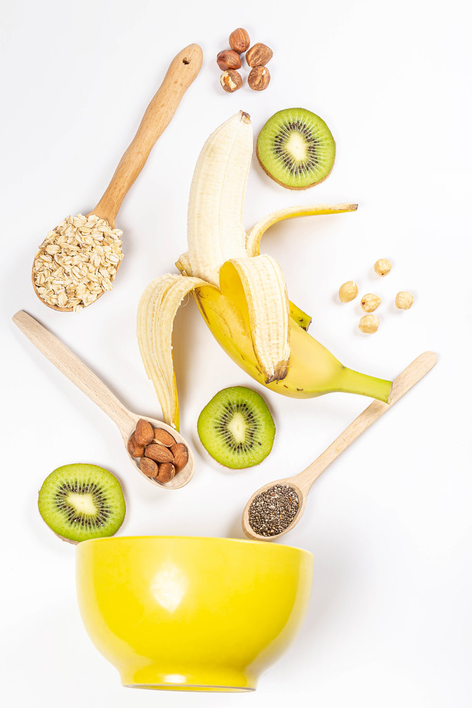Banana, kiwi, nuts, chia seeds and oatmeal with yellow bowl, top view