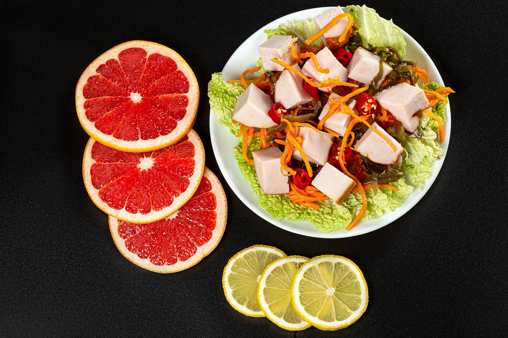 Top view salad with vegetables and chicken on black background with sliced grapefruit and lemon