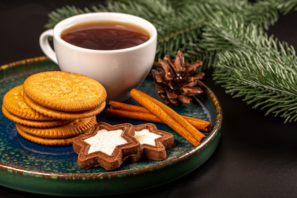Christmas background with cookies, a cup of coffee, cinnamon sticks and branches of a christmas tree