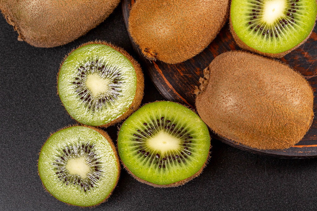 Whole and sliced kiwi fruit, top view