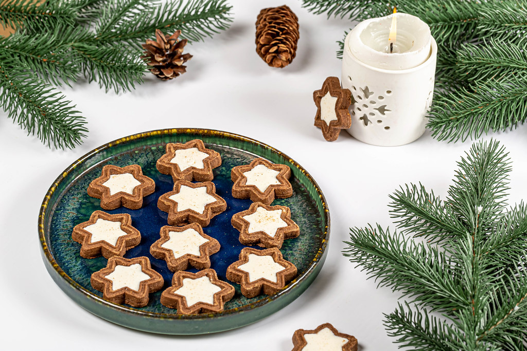 Chocolate star cookies with branches of a christmas tree and burning candles