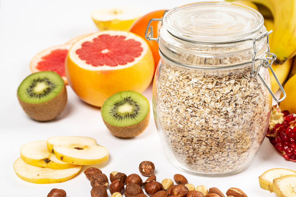 Close-up of a jar of oatmeal and slices of fresh colorful fruits on a white background with nuts