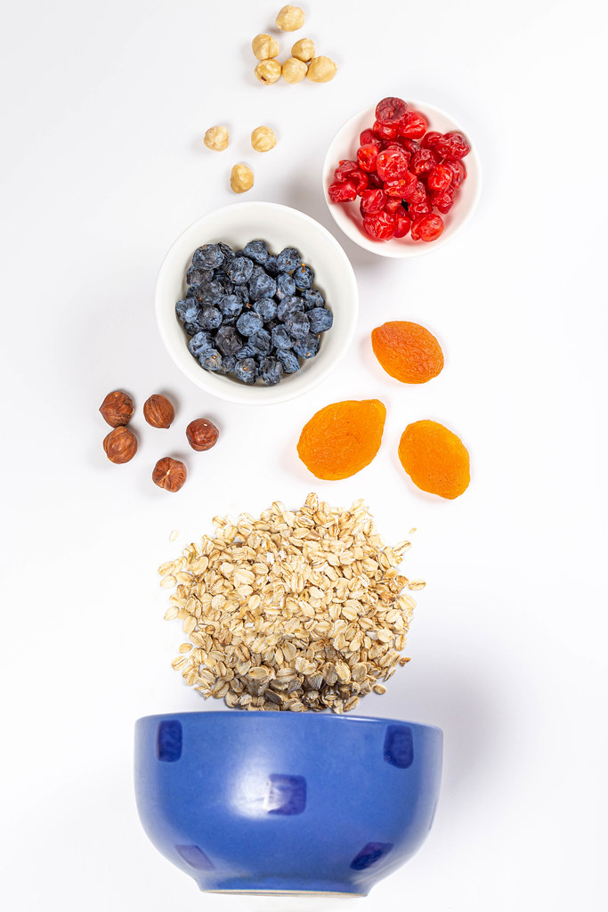Blue bowl with raw oatmeal, dried berries and nuts, top view