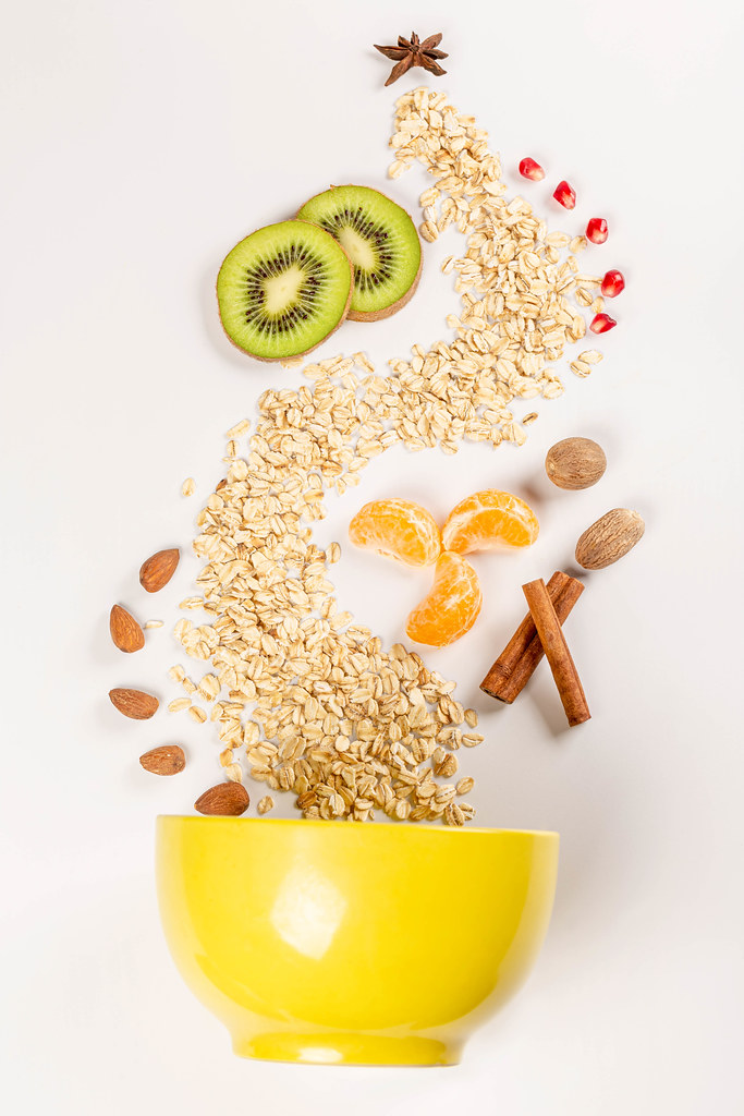 Top view, yellow bowl with scattered ingredients for making healthy breakfast