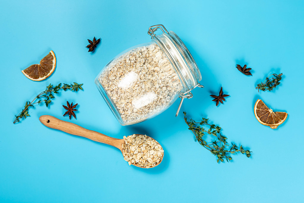 Top view of jar and wooden spoon with oatmeal on blue background with thyme, star anise, dried orange