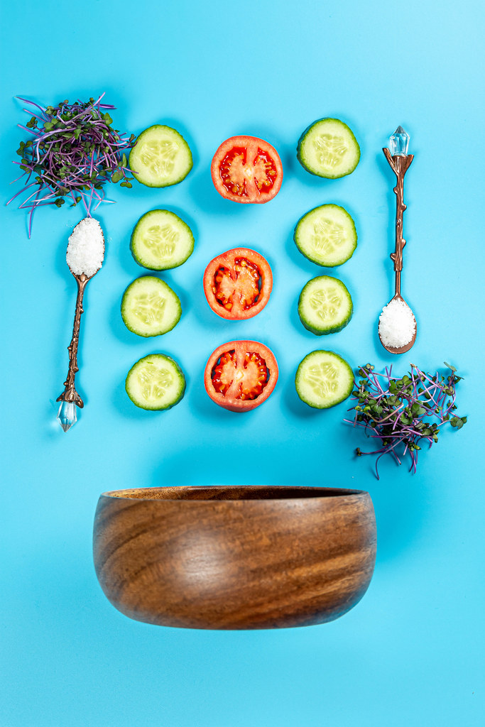 Top view, wooden bowl with ingredients for salad on blue background