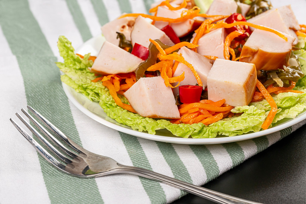 Plate with salad from carrots, lettuce, seaweed, chicken and chili